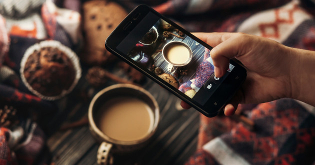 A hand holding a smartphone taking a picture of a cup of coffee.