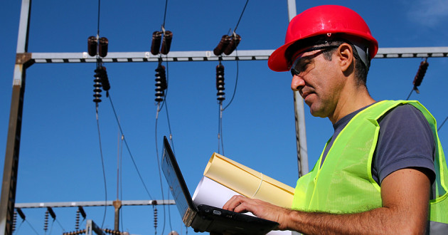 An engineer using a laptop next to an electrical tower.