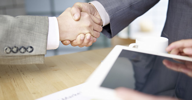 Two business associates shaking hands while a third holds a digital tablet.