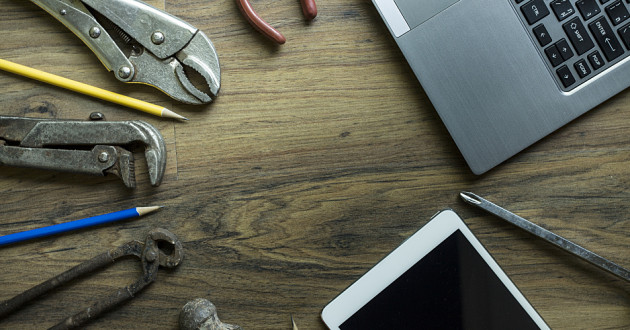 Tools, pencils and electronic devices on a wooden table.