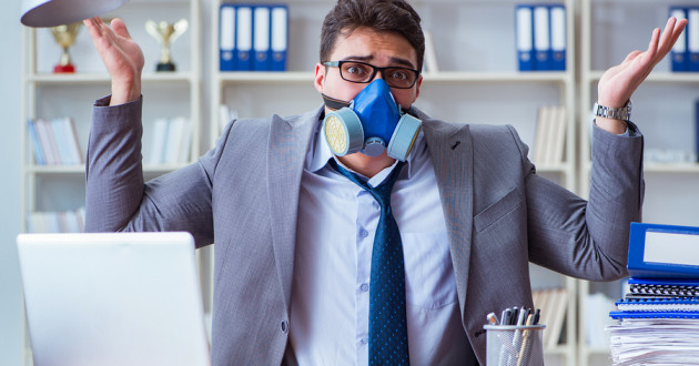 A person wearing a gas mask while using a laptop in an office.