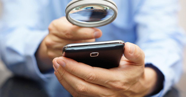 A businessman examining a smartphone through a magnifying glass.