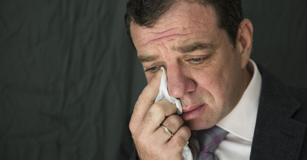 A businessman wiping tears with a piece of facial tissue.