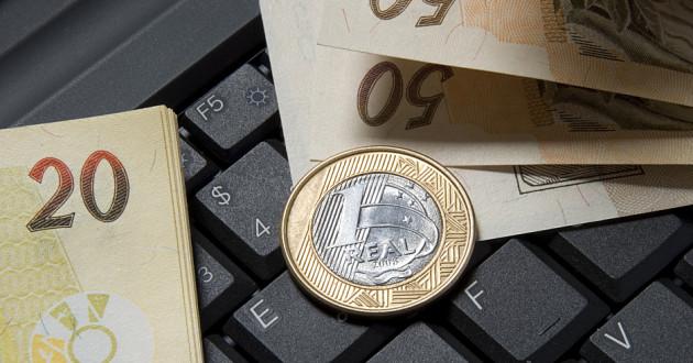 Brazilian currency on a computer keyboard.