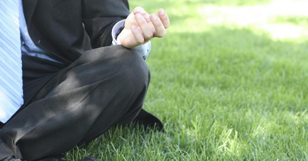 A businessman meditating outdoors.