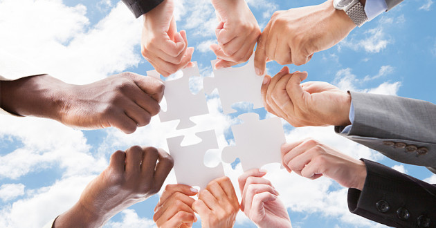 A group of professionals holding white puzzle pieces against a backdrop of clouds in a blue sky.