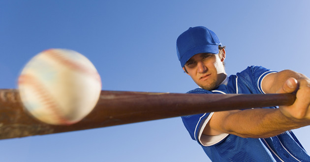 A baseball player swinging a bat to make contact with a baseball.