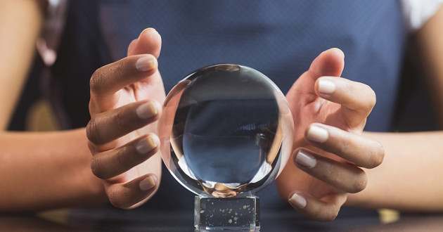 A woman holding her hands around a crystal ball on a desk.