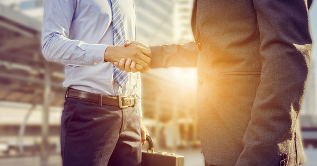 Two businesspeople shaking hands outdoors.