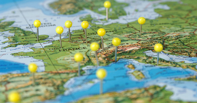 Yellow pins stuck in a map of Europe.