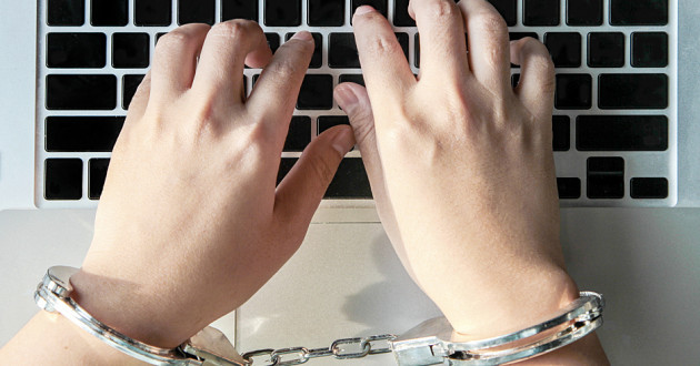 Two hands typing on a laptop keyboard while locked in handcuffs.