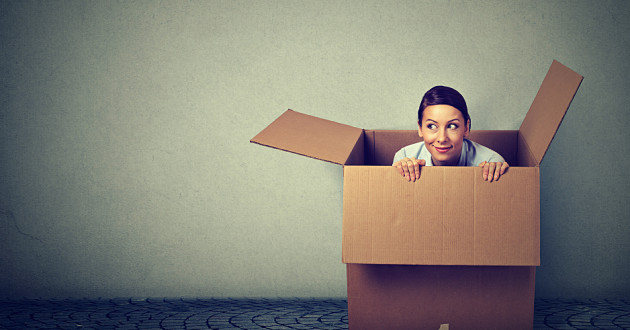 A woman crouching in a cardboard box.