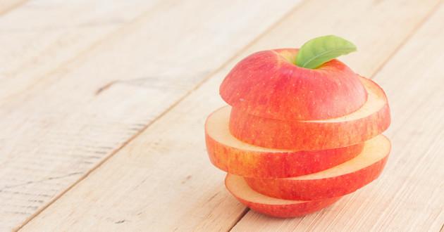 An apple cut into four slices.