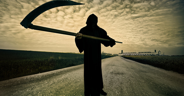 A Grim Reaper figure standing on a road.