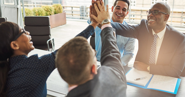 Business colleagues joining hands in a gesture of collaboration.