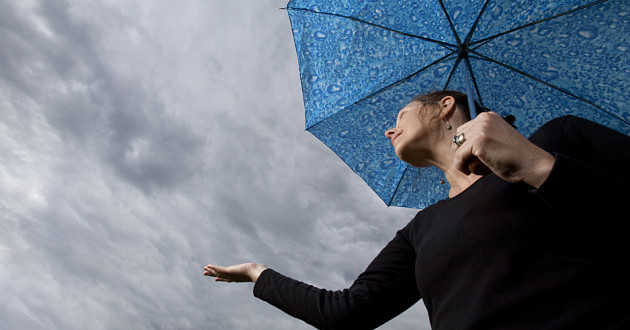 A woman holding an umbrella and looking up at an overcast sky.