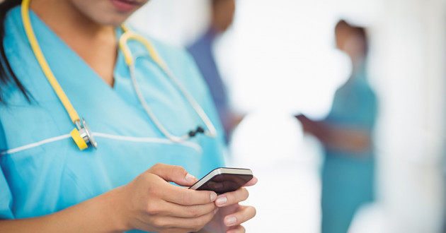 A health care employee using a smartphone.