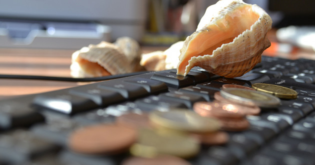 Seashells and coins on a desktop computer keyboard.