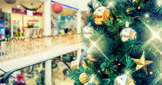 Christmas tree with gold decorations in shopping mall.