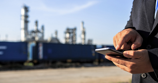 A businessman using a smartphone in front of an oil rig.