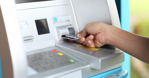 A close-up of a hand inserting a card at an ATM.