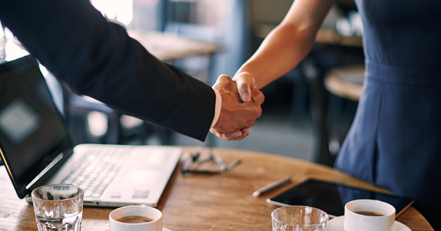 Two businesspeople shaking hands in a cafe.