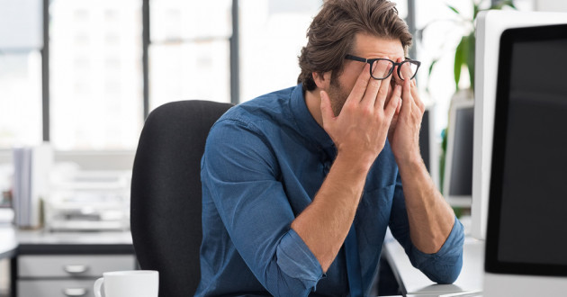 Frustrated businessman rubbing his forehead in front of a computer.