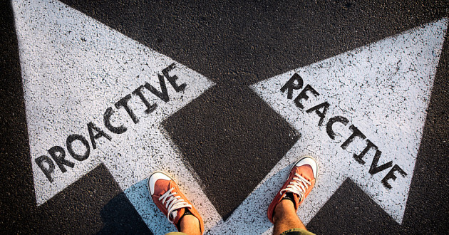 "A person standing on two white arrows labeled ""proactive"" and ""reactive."""