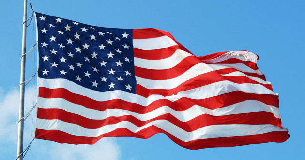 An American flag flying in the wind against a blue sky.