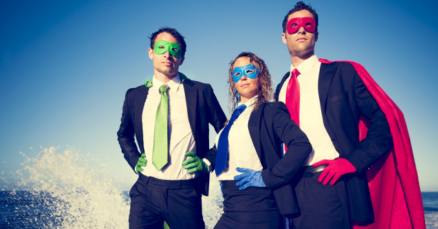 Three businesspeople wearing multicolored capes, masks and gloves.