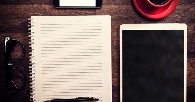 Blank notepad and tablet on table.