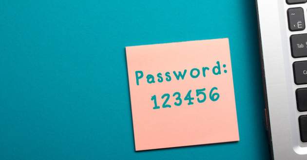 "The word ""Password"" written on a pink adhesive note card next to a computer keyboard."
