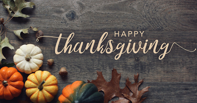 Happy Thanksgiving greeting text with pumpkins, squash and leaves over dark wood background.