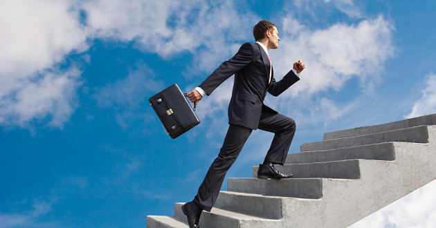 A businessman climbing a staircase to the clouds.