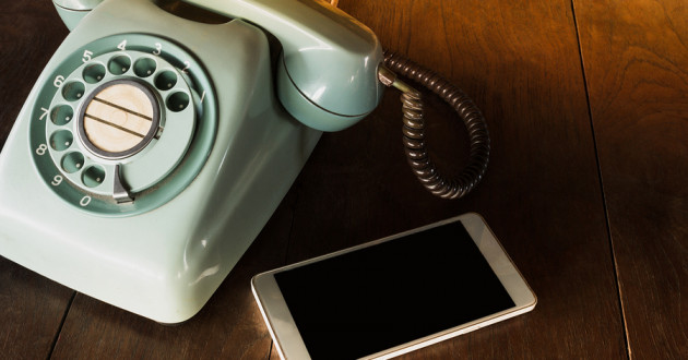 A rotary phone and a smartphone on a wooden surface.