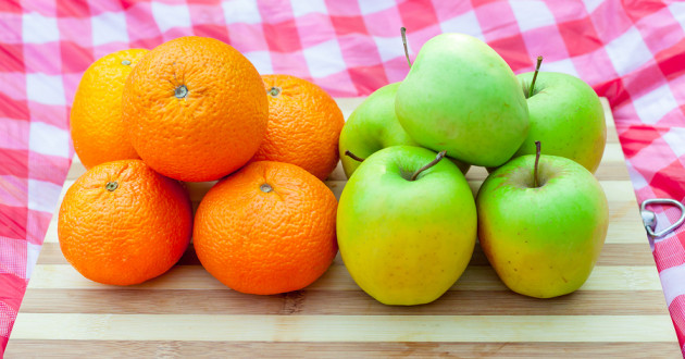 A pile of five oranges beside a pile of five green apples on a cutting board.