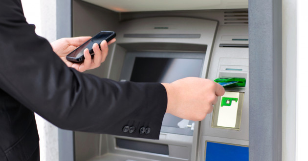 A person inserting a payment card into an ATM machine.