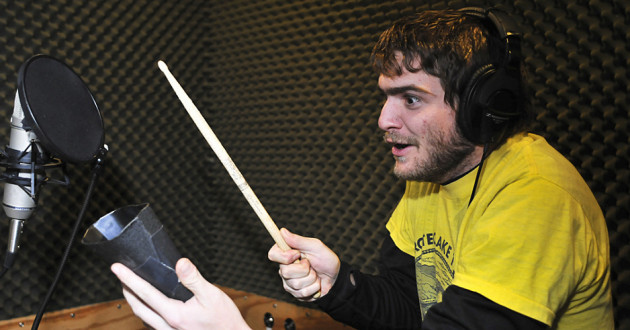 A percussionist playing a cowbell in a recording studio.