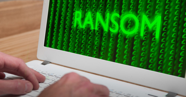 "A person typing on a laptop while the word ""Ransom"" flashes across the screen."