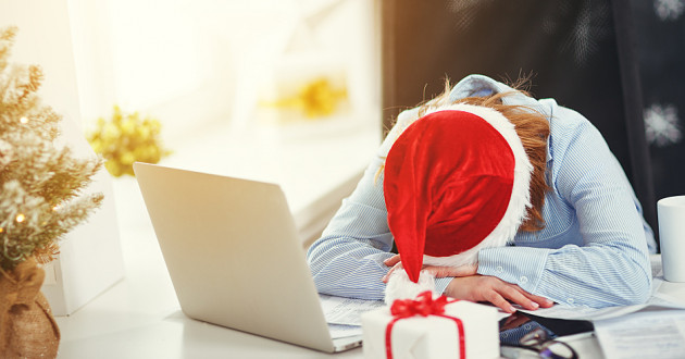 A woman wearing a Santa hat with her head down in front of a laptop.