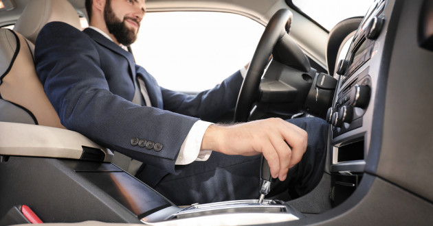 A man in a suit sitting in the driver's seat of a car.