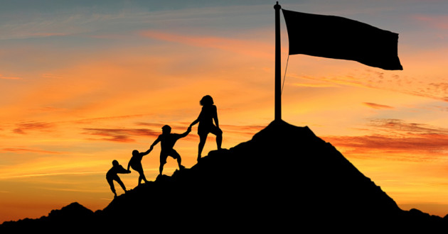 Silhouettes of four people climbing up a mountain to reach a flag.