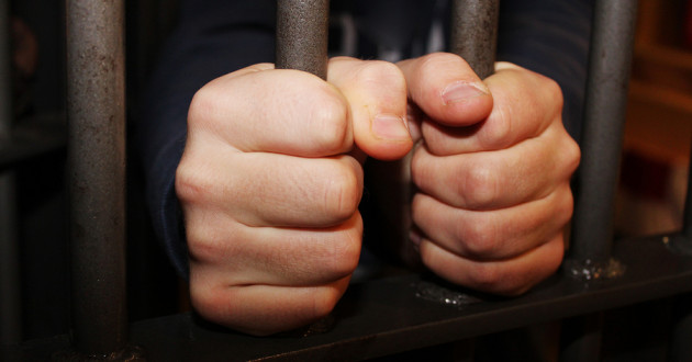 Two hands gripping the bars of a jail cell.