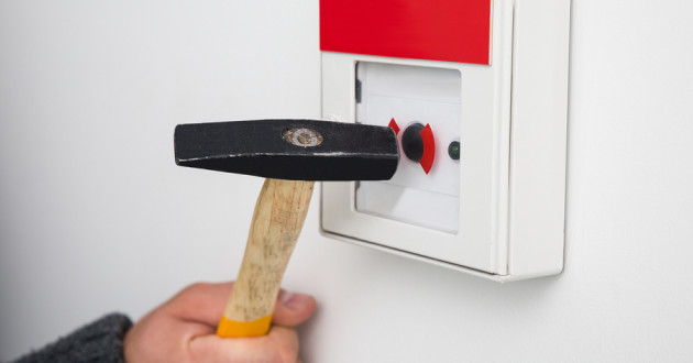 A hand using a hammer to break the glass casing on a fire alarm.