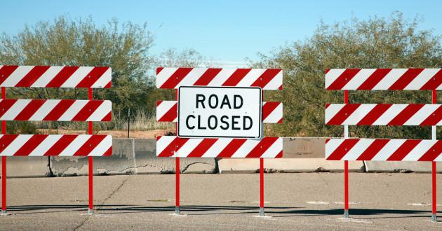 Three roadblocks lined up on a street.