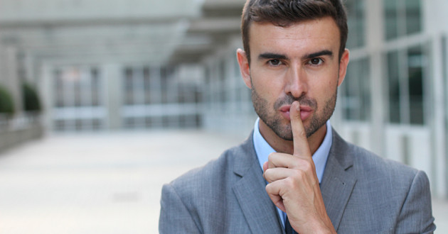 A businessman holding his index finger to his lips.