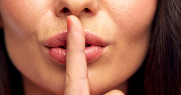 A woman holding a finger to her lips.