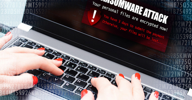 A woman typing on a laptop that has been infected with ransomware.