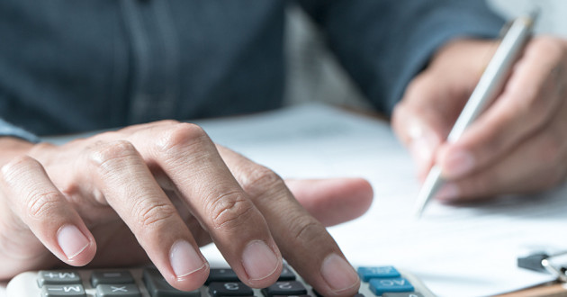 A person using a calculator with one hand and writing with the other.
