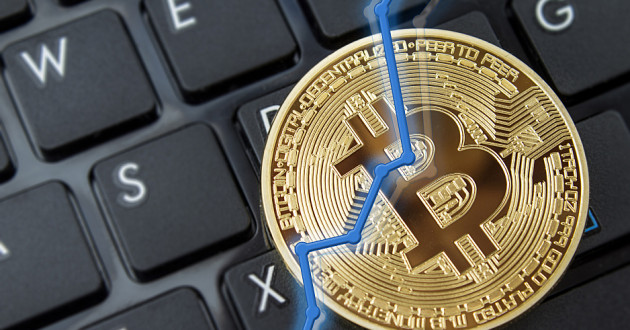 A physical representation of a bitcoin on a computer keyboard with a graph line suggesting growth.